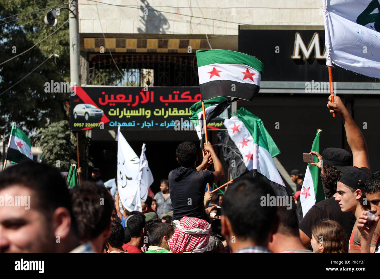 People seen with flags during a protest in the town of Eriha in Idlib calling for the release of detainees held by the Syrian regime. - Stock Image