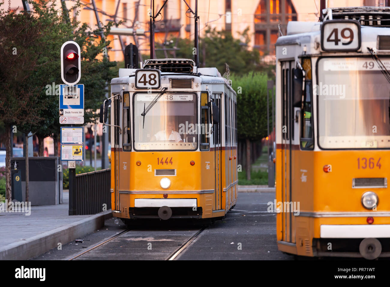 Two trams drive past one another in the center of Budapest, Hungary Stock Photo
