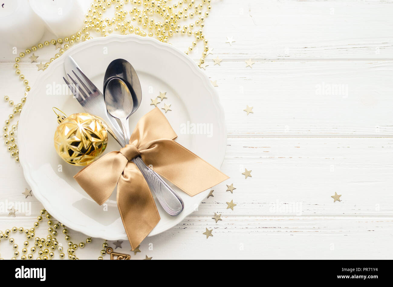 Festive place setting for christmas dinner on white rustic