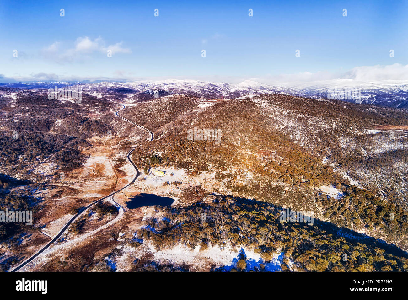 Distant mountains peaks covered by white snow in winter season high in Snowy mountains of australia - popular skiing and snowboarding resort of Perish - Stock Image
