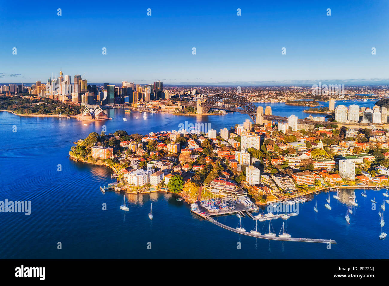 Rich blue waters of Sydney harbour reflecting clear blue sky around major Sydney city landmarks seen from above over Kirribilli yacht club towards the - Stock Image