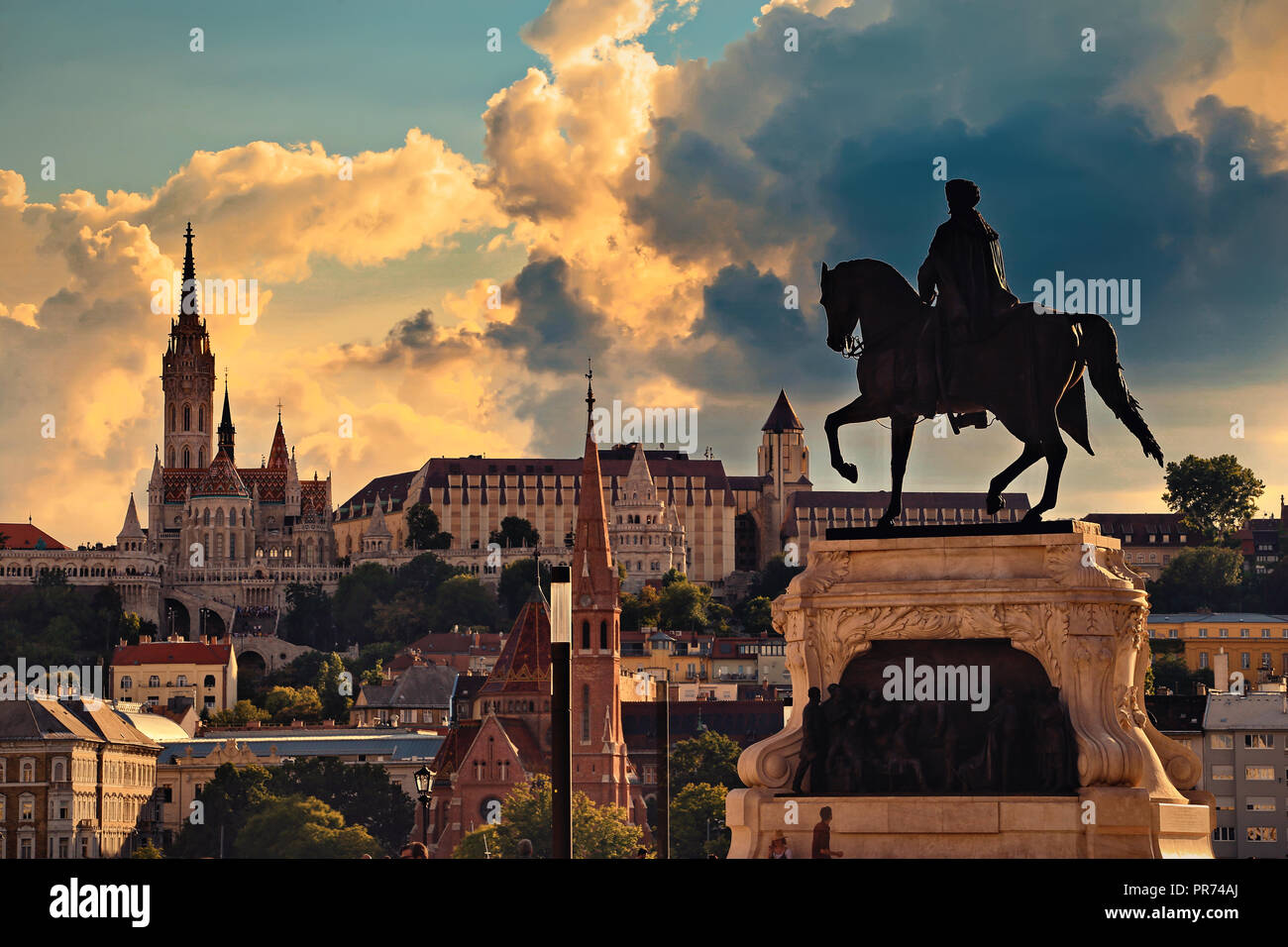 Sunset city skyline of Budapest. Matthias Church, Fisherman's Bastion and other historical buildings on Castle Hill with statue of Gyula Andrassy. Stock Photo