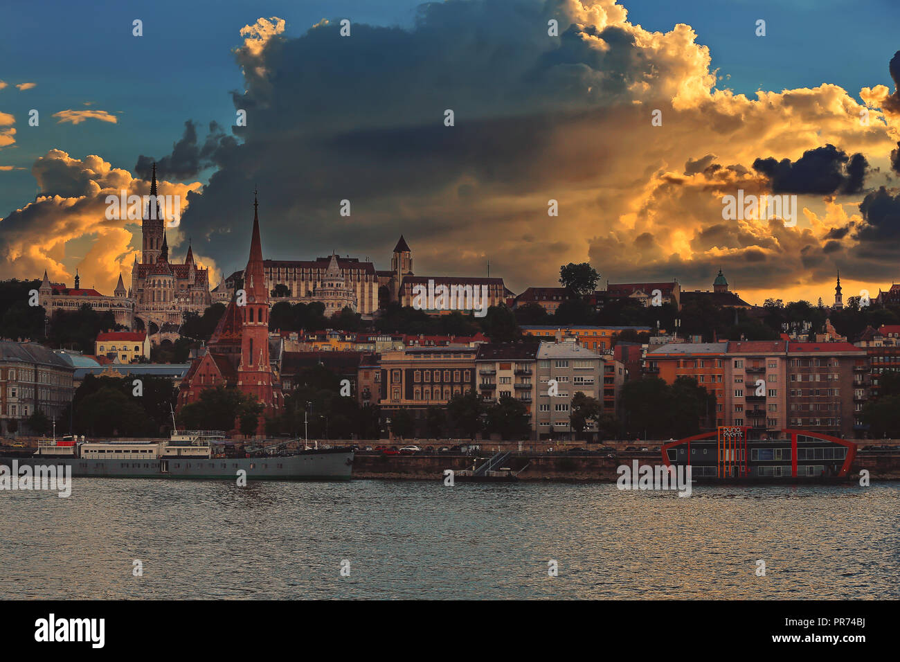 Sunset city skyline of Budapest. Matthias Church, Fisherman's Bastion and other historical buildings on Castle hill. View from Danube - Stock Image