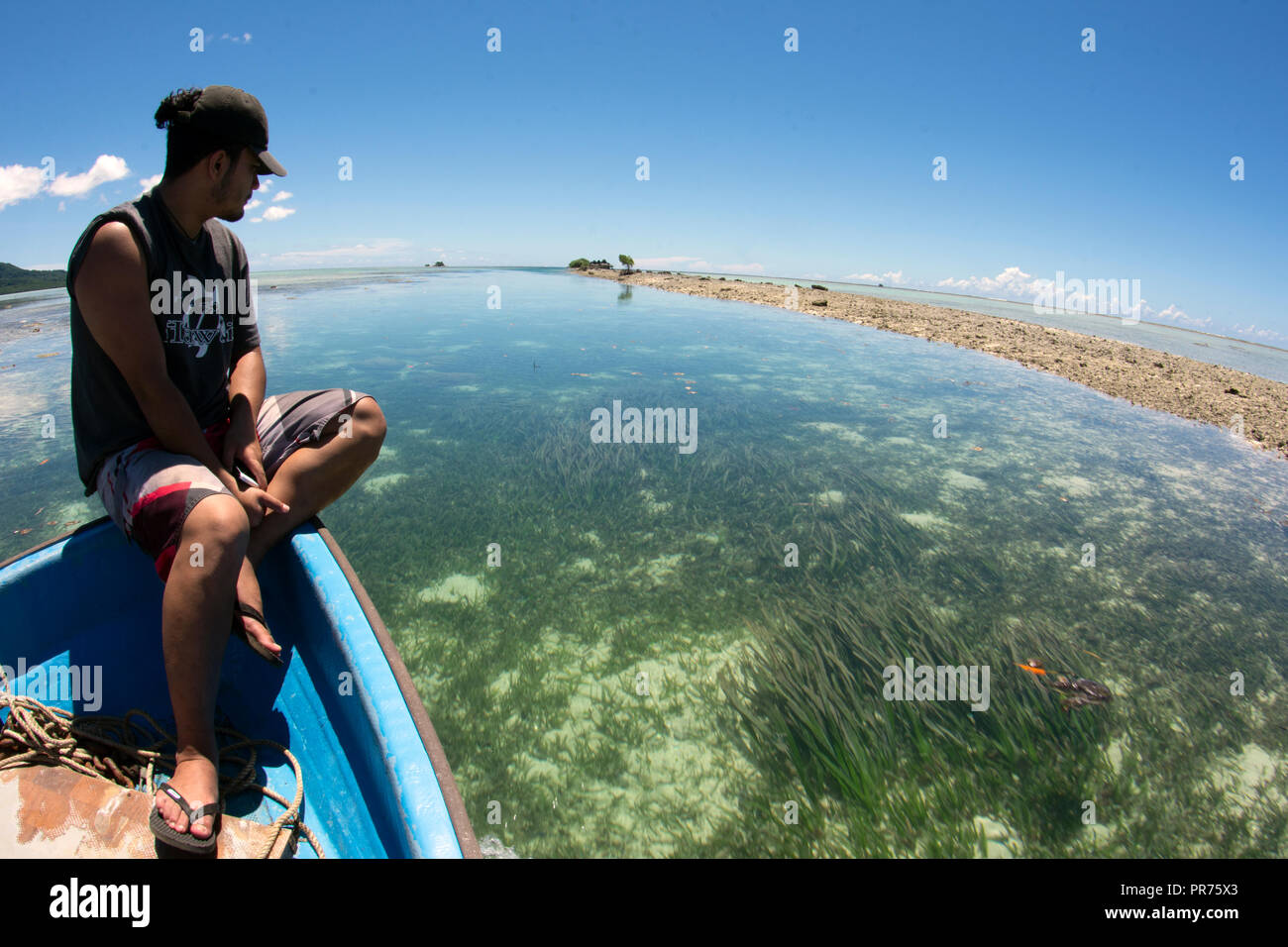 Micronesian man on a boat ride over a seagrass bed in the lagoon of Pohnpei, Federated States of Micronesia - Stock Image