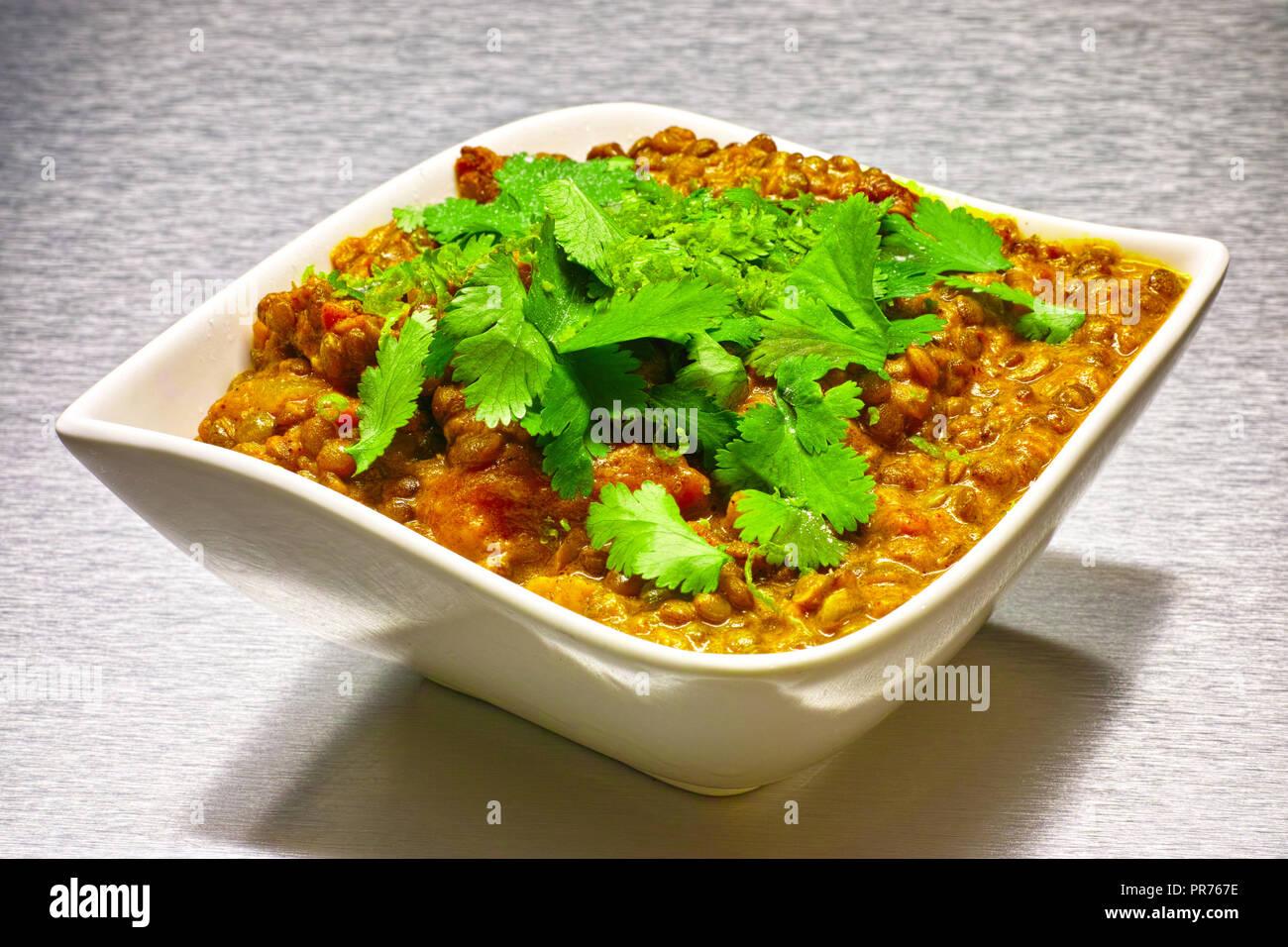 Moong Dahl, indian vegetarian lentil soup, in white bowl. Aluminium background. Stock Photo