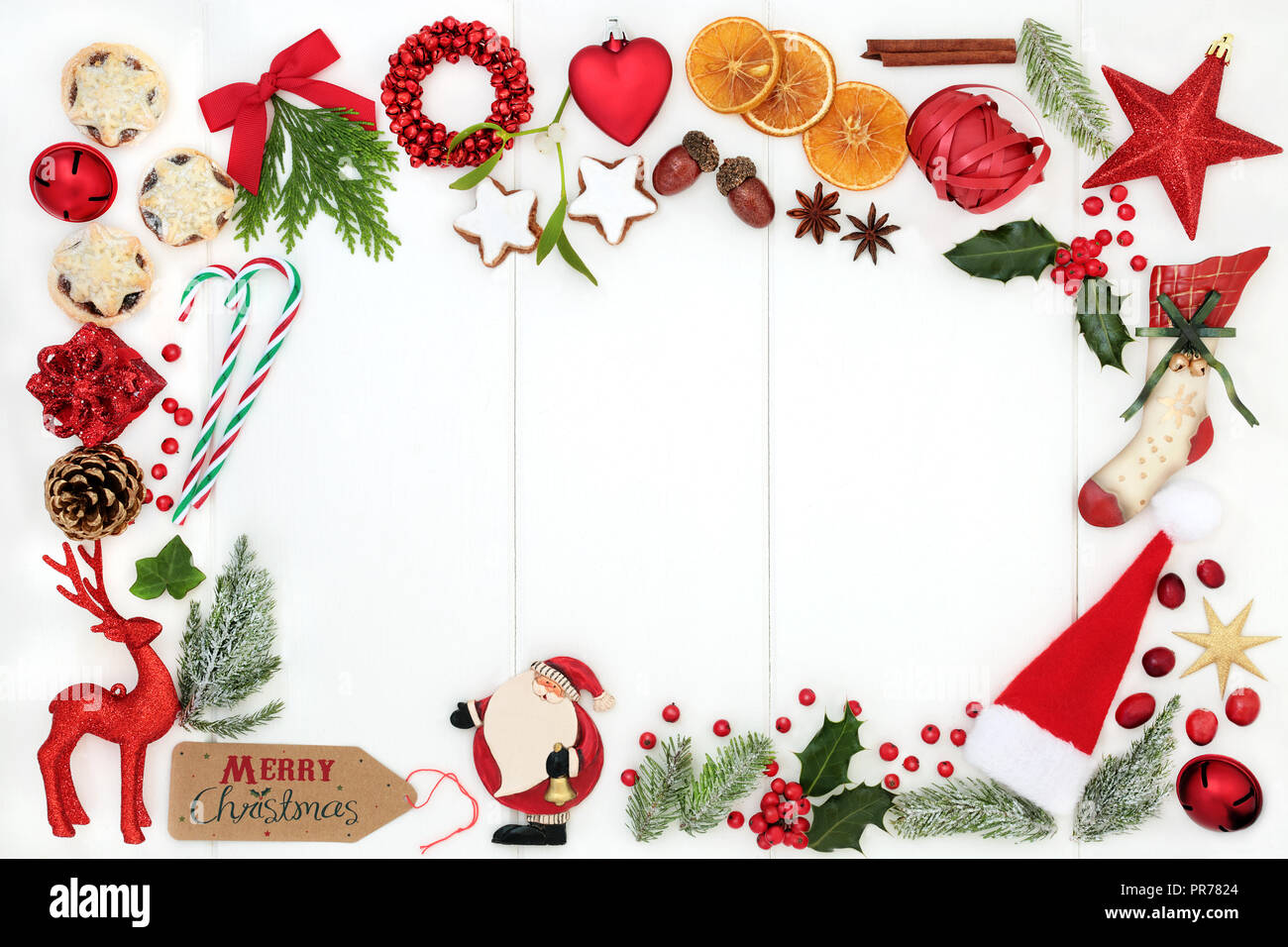 Christmas background border composition with traditional symbols of bauble tree decorations, candy canes, mince pies, fruit, spices & winter flora. - Stock Image