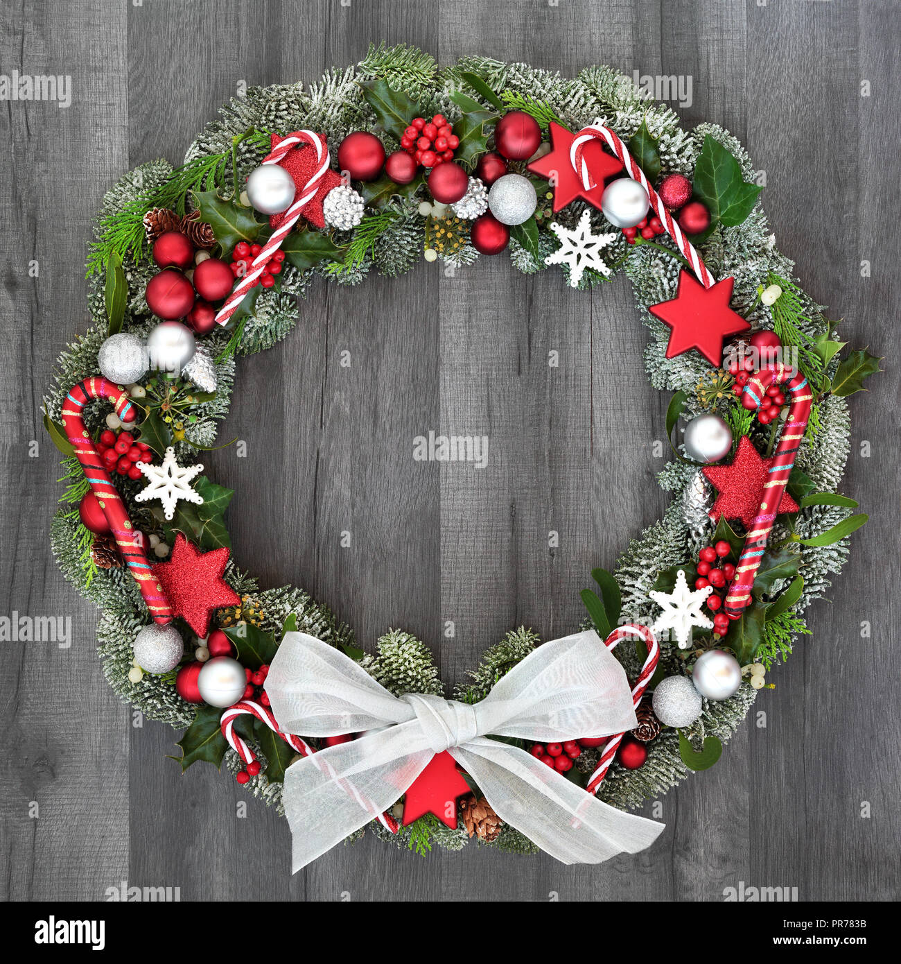 Christmas And Winter Wreath With Candy Canes Bow Bauble Decorations Holly Mistletoe Ivy And Spruce Fir On Rustic Grey Wood Background Stock Photo Alamy