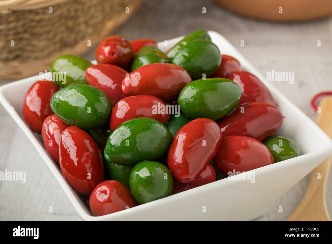 Bowl with red and green Italan bella di cerignola olives - Stock Image