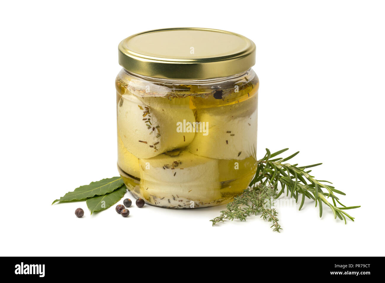 Glass jar with preserved white organic Dutch goat cheese and fresh herbs isolated on white background - Stock Image