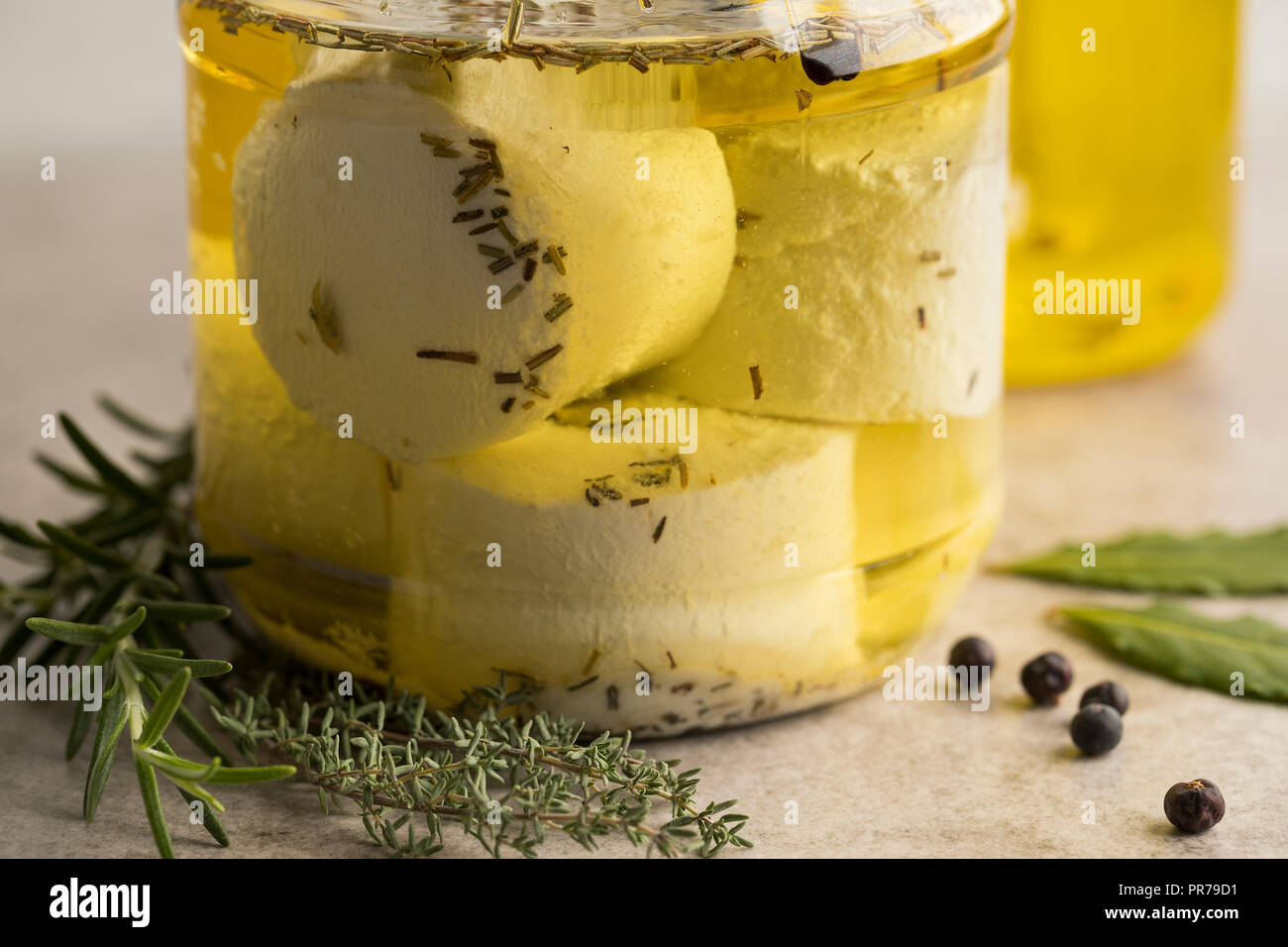 Glass jar with preserved white organic Dutch goat cheese and fresh herbs close up - Stock Image