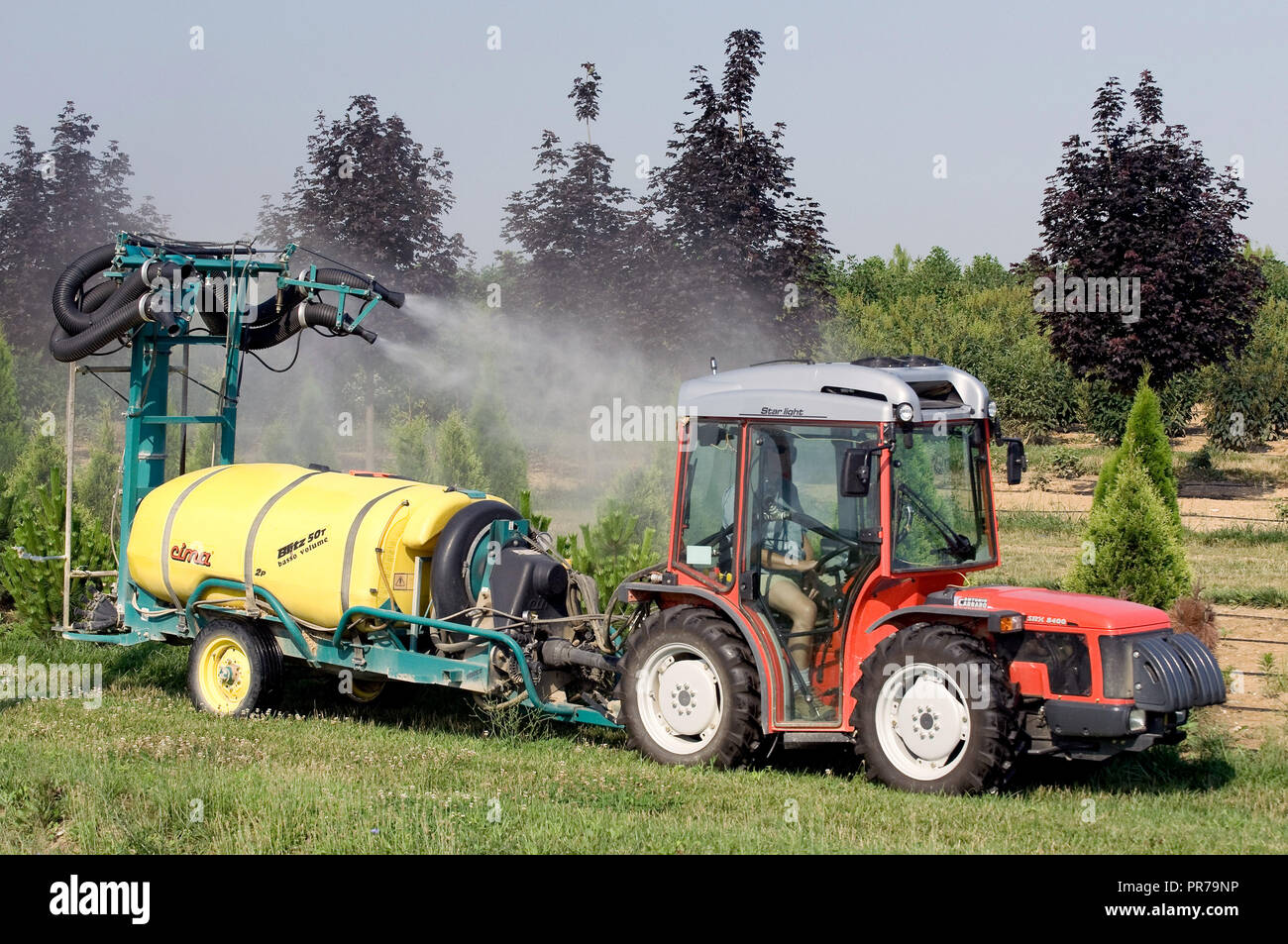 2008 - Farmer driving an Antonio Carraro SRX 8400 tractor and pulling a pesticide sprayer spraying trees on a tree farm (orchard) - Stock Image