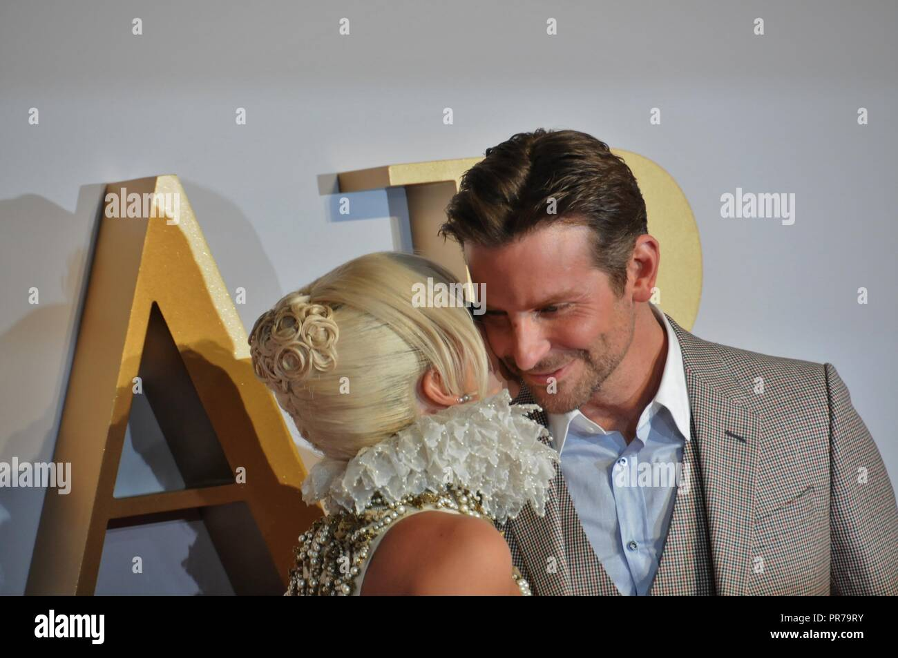 Lady Gaga kisses Bradley Cooper, at the London film premier of A Star is Born. Stock Photo