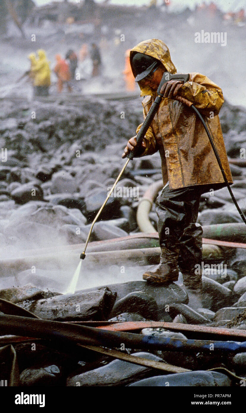 Worker cleaning oil-covered rocks using high-pressure spray