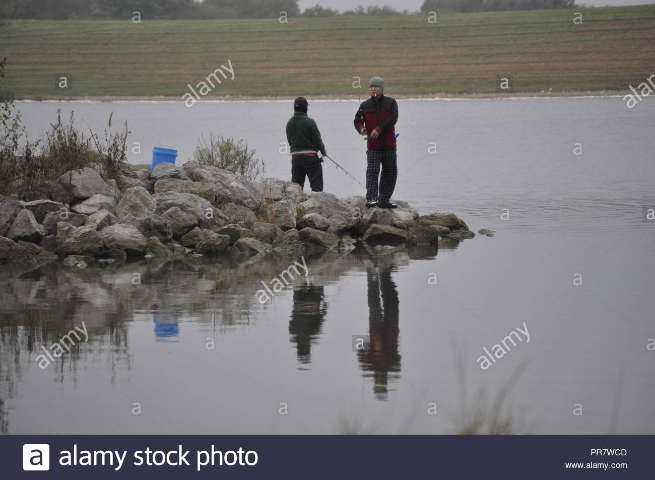 Two Asian fisherman at Holmes Lake Park in Lincoln.  The weather was foul, but they fished on and appeared to be enjoying themselves. - Stock Image