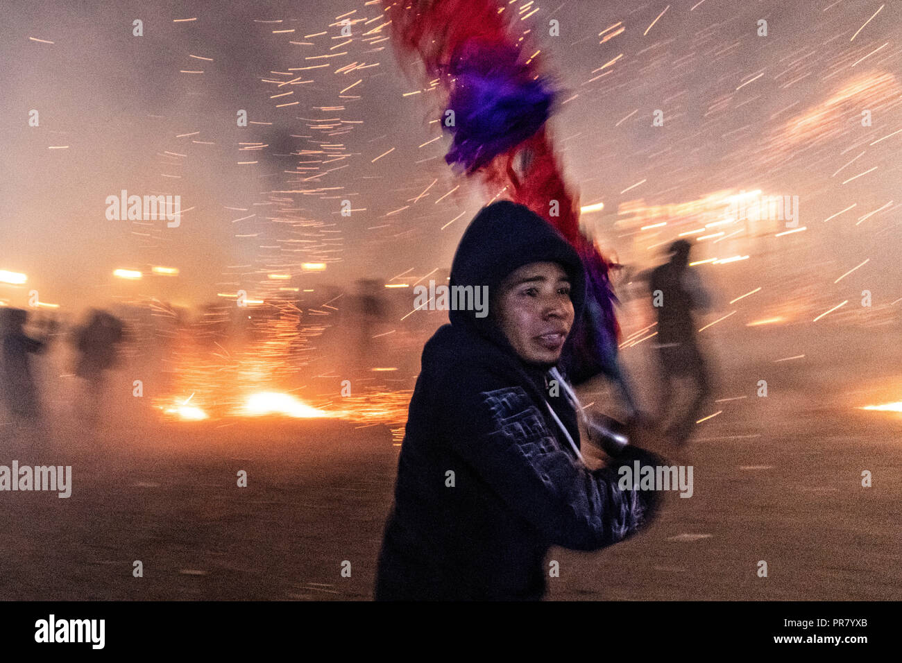 San Miguel de Allende, Mexico. 29th Sept 2018. A Mexican man runs for cover as he is barraged by pyrotechnic sky rockets during the Alborada festival September 29, 2018 in San Miguel de Allende, Mexico. The unusual festival celebrates the cities patron saint with a two hour-long firework battle at 4am representing the struggle between Saint Michael and Lucifer. Credit: Planetpix/Alamy Live News - Stock Image