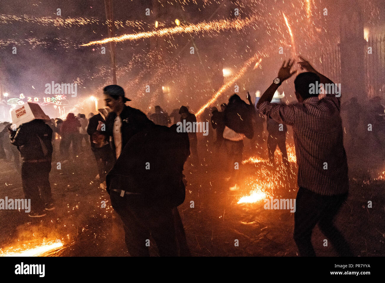 San Miguel de Allende, Mexico. 29th Sept 2018. Mexicans run for cover as they are barraged by pyrotechnic sky rockets during the Alborada festival September 29, 2018 in San Miguel de Allende, Mexico. The unusual festival celebrates the cities patron saint with a two hour-long firework battle at 4am representing the struggle between Saint Michael and Lucifer. Credit: Planetpix/Alamy Live News - Stock Image