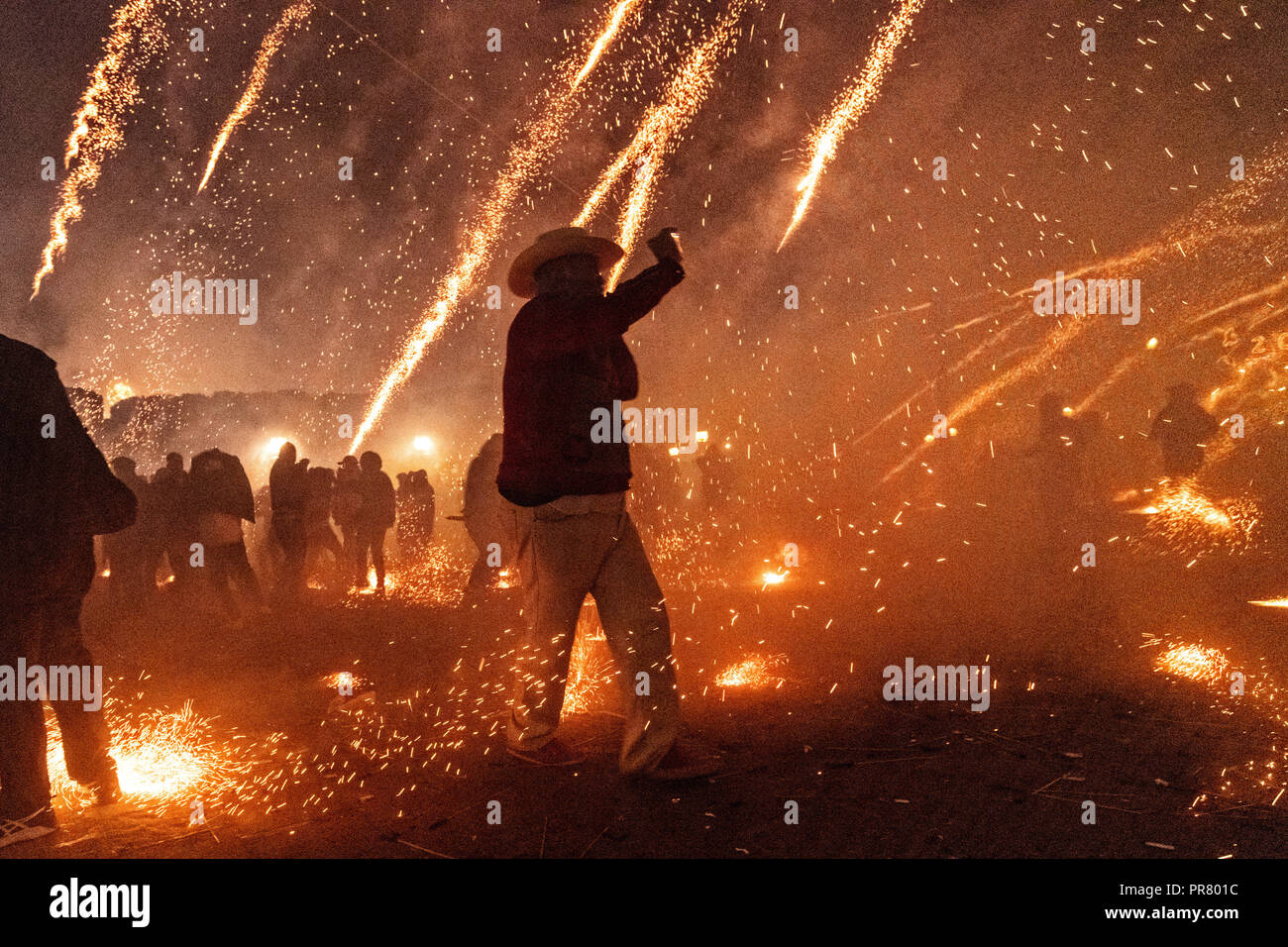 San Miguel de Allende, Mexico. 29th Sept 2018. Sparks from exploding sky rockets scatter as a Mexican cowboy stands in the middle taking a mobile phone photo during the Alborada festival September 29, 2018 in San Miguel de Allende, Mexico. The unusual festival celebrates the cities patron saint with a two hour-long firework battle at 4am representing the struggle between Saint Michael and Lucifer. Credit: Planetpix/Alamy Live News - Stock Image
