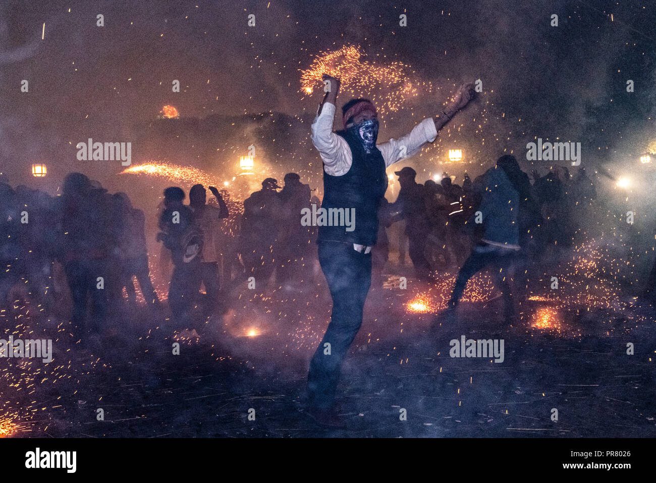 San Miguel de Allende, Mexico. 29th Sept 2018. A Mexican man wearing a protective mask dances during a barrage of sky rockets during the Alborada festival September 29, 2018 in San Miguel de Allende, Mexico. The unusual festival celebrates the cities patron saint with a two hour-long firework battle at 4am representing the struggle between Saint Michael and Lucifer. Credit: Planetpix/Alamy Live News - Stock Image