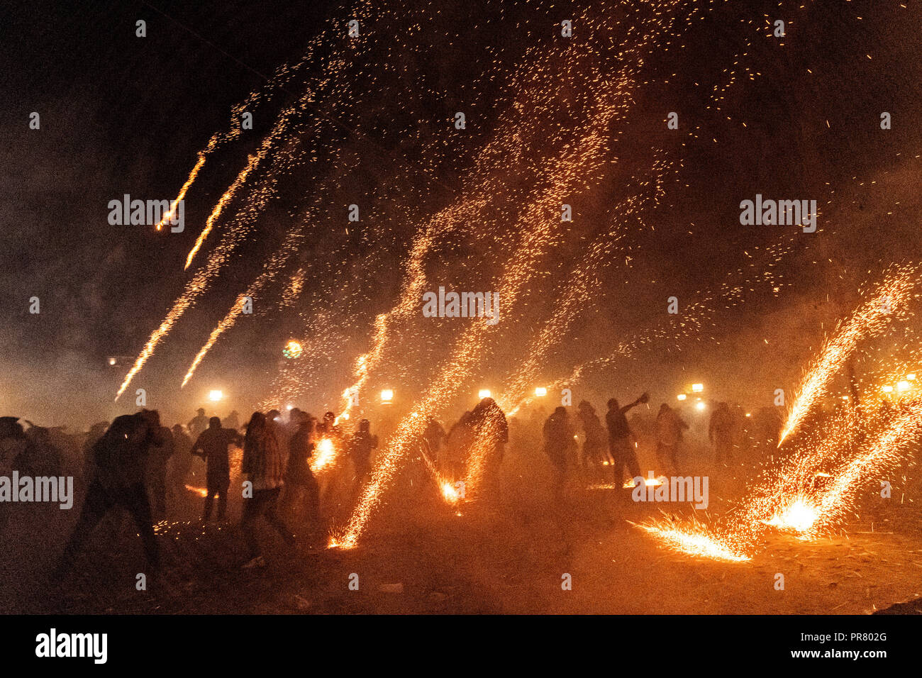 San Miguel de Allende, Mexico. 29th Sept 2018. Sparks from exploding sky rockets scatter as Mexicans run for cover during a barrage of pyrotechnic rockets during the Alborada festival September 29, 2018 in San Miguel de Allende, Mexico. The unusual festival celebrates the cities patron saint with a two hour-long firework battle at 4am representing the struggle between Saint Michael and Lucifer. Credit: Planetpix/Alamy Live News - Stock Image