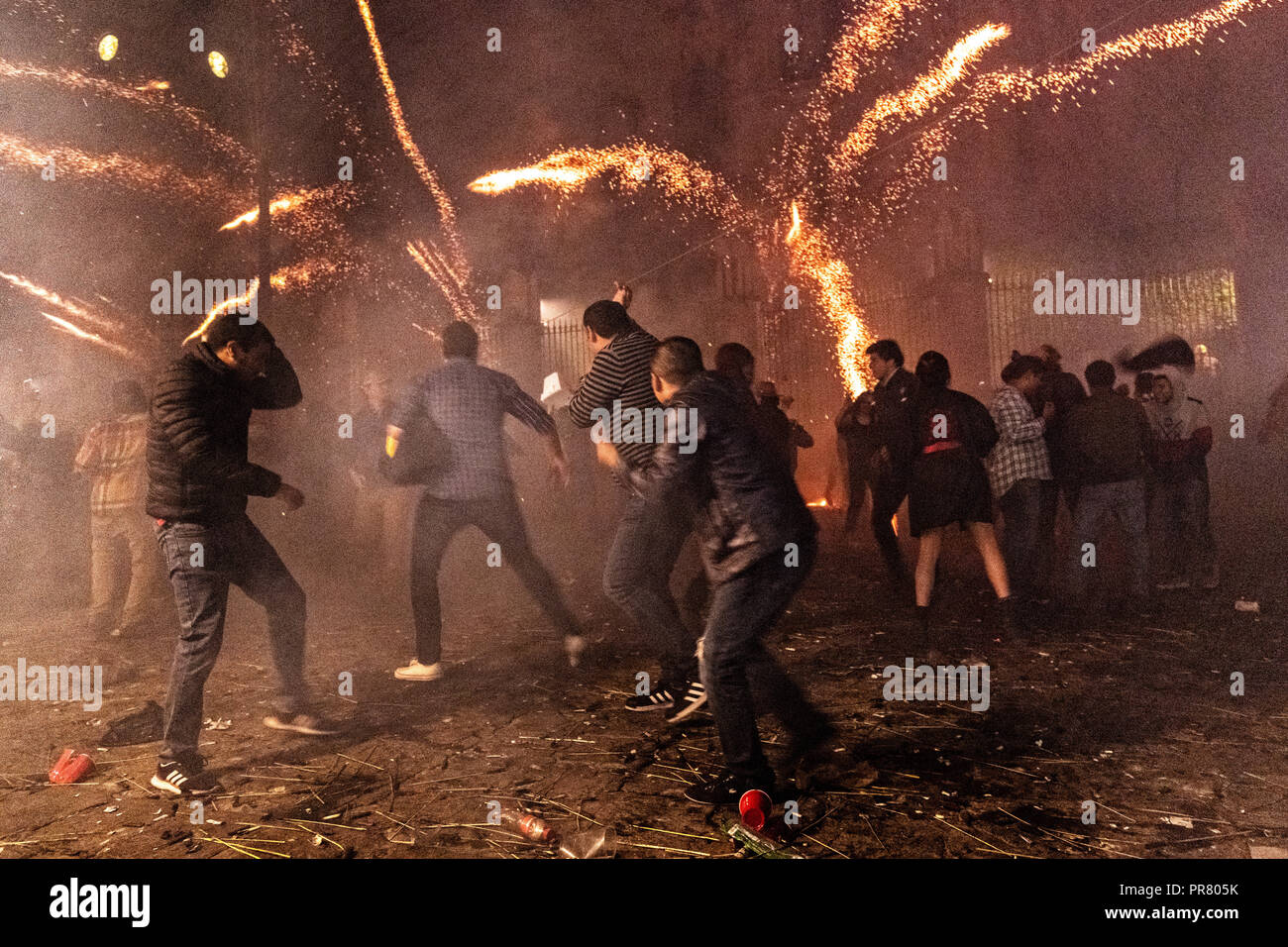 San Miguel de Allende, Mexico. 29th Sept 2018. Residents scramble as they are pelted by pyrotechnic rockets during the Alborada festival September 29, 2018 in San Miguel de Allende, Mexico. The unusual festival celebrates the cities patron saint with a two hour-long firework battle at 4am representing the struggle between Saint Michael and Lucifer. Credit: Planetpix/Alamy Live News - Stock Image