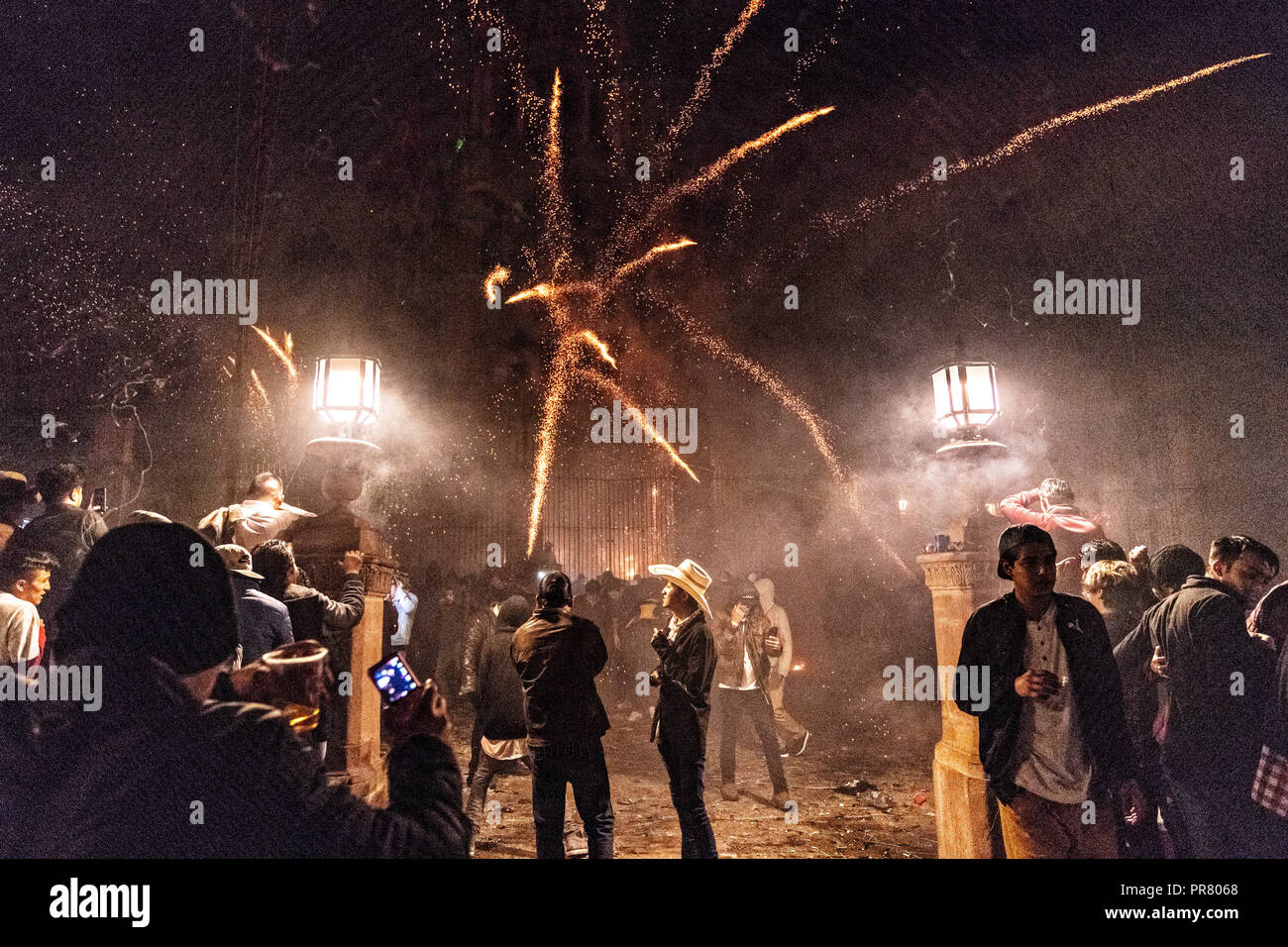 San Miguel de Allende, Mexico. 29th Sept 2018. A group of onlookers watch a barrage of sky rockets explode from relative safety during the Alborada festival September 29, 2018 in San Miguel de Allende, Mexico. The unusual festival celebrates the cities patron saint with a two hour-long firework battle at 4am representing the struggle between Saint Michael and Lucifer. Credit: Planetpix/Alamy Live News - Stock Image