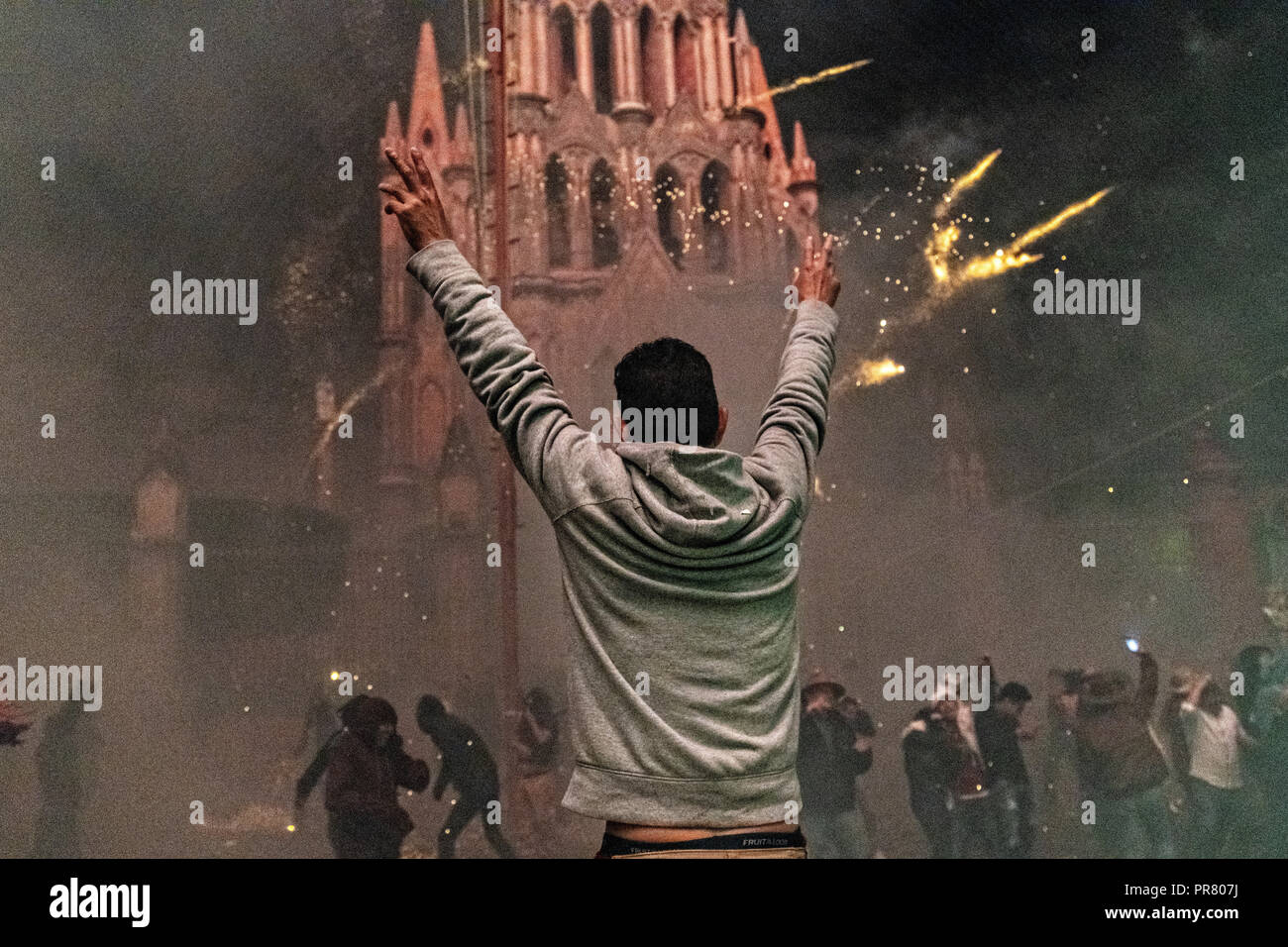 San Miguel de Allende, Mexico. 29th Sept 2018. A Mexican man holds his arms up at the San Miguel Archangel church during a barrage of sky rockets at the Alborada festival September 29, 2018 in San Miguel de Allende, Mexico. The unusual festival celebrates the cities patron saint with a two hour-long firework battle at 4am representing the struggle between Saint Michael and Lucifer. Credit: Planetpix/Alamy Live News - Stock Image