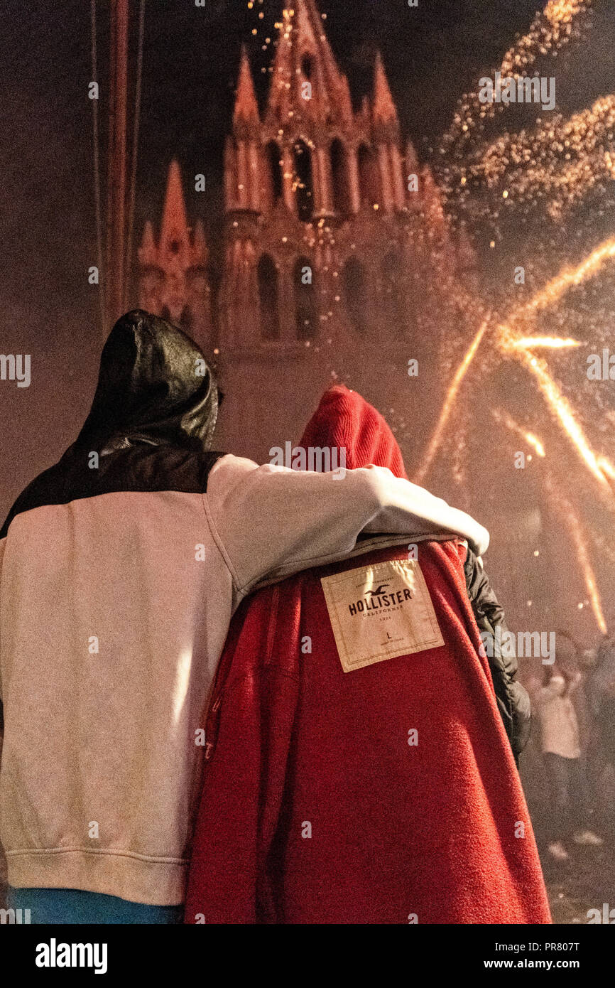 San Miguel de Allende, Mexico. 29th Sept 2018. A couple embrace as they watch sky rockets explode around them in front of the San Miguel Archangel church during the Alborada festival September 29, 2018 in San Miguel de Allende, Mexico. The unusual festival celebrates the cities patron saint with a two hour-long firework battle at 4am representing the struggle between Saint Michael and Lucifer. Credit: Planetpix/Alamy Live News - Stock Image