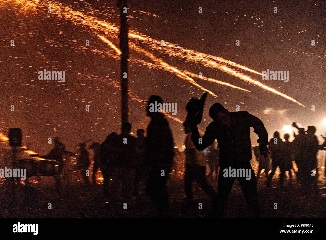 San Miguel de Allende, Mexico. 29th Sept 2018. Sparks from exploding sky rockets scatter as Mexicans run for cover during a barrage of pyrotechnic rockets at the Alborada festival September 29, 2018 in San Miguel de Allende, Mexico. The unusual festival celebrates the cities patron saint with a two hour-long firework battle at 4am representing the struggle between Saint Michael and Lucifer. Credit: Planetpix/Alamy Live News - Stock Image