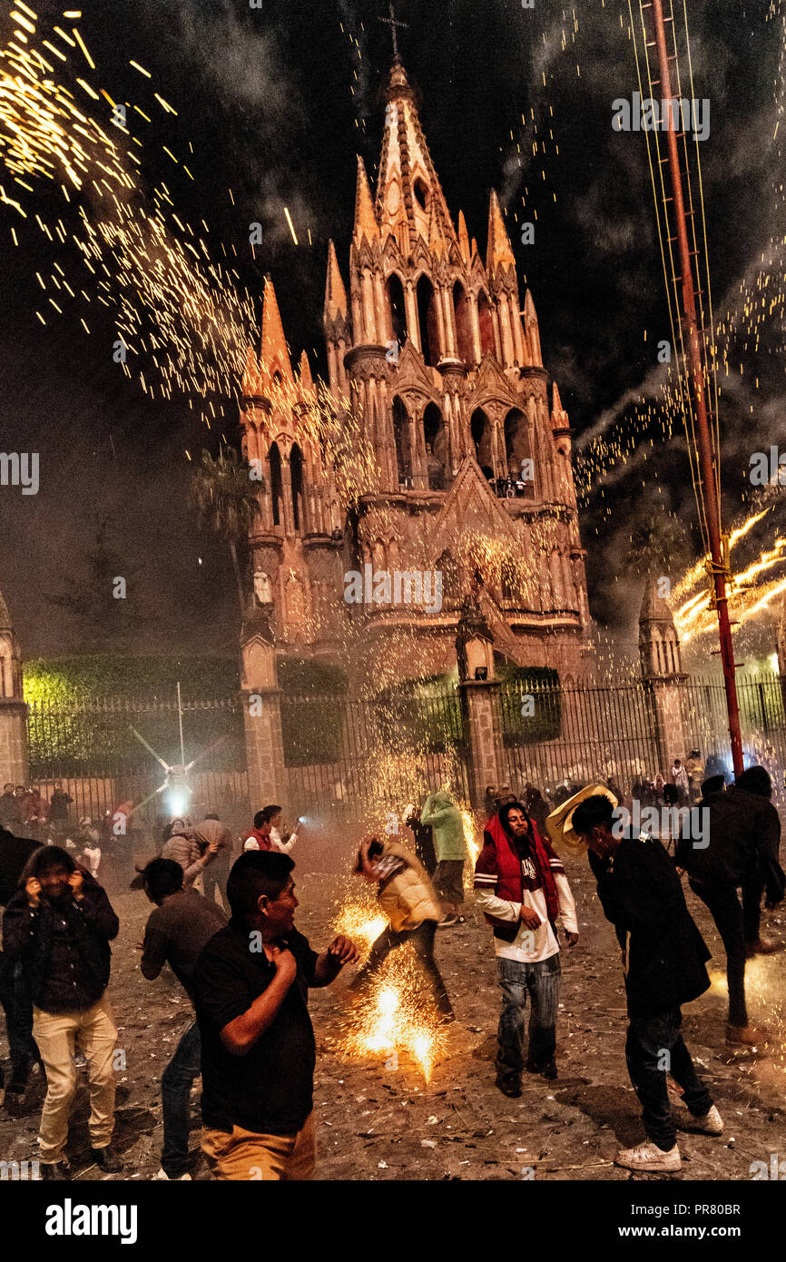 San Miguel de Allende, Mexico. 29th Sept 2018. Residents scramble as they are pelted by pyrotechnic rockets in front of the Saint Michael Archangel church during the Alborada festival September 29, 2018 in San Miguel de Allende, Mexico. The unusual festival celebrates the cities patron saint with a two hour-long firework battle at 4am representing the struggle between Saint Michael and Lucifer. Credit: Planetpix/Alamy Live News - Stock Image