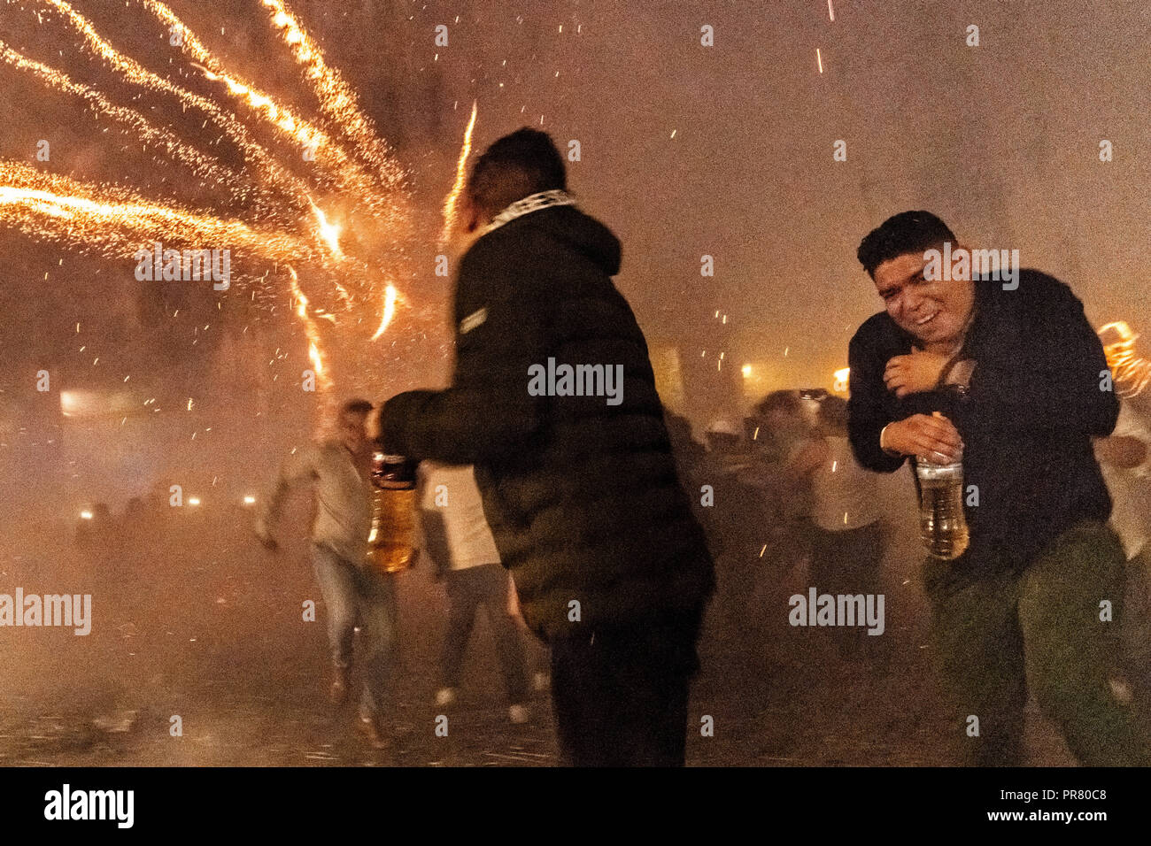 San Miguel de Allende, Mexico. 29th Sept 2018. Mexican men carrying bottles of tequila scramble as they are pelted by pyrotechnic rockets during the Alborada festival September 29, 2018 in San Miguel de Allende, Mexico. The unusual festival celebrates the cities patron saint with a two hour-long firework battle at 4am representing the struggle between Saint Michael and Lucifer. Credit: Planetpix/Alamy Live News - Stock Image