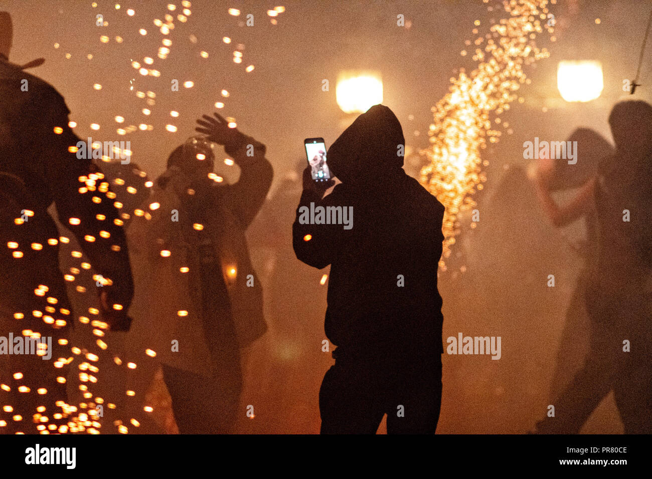 San Miguel de Allende, Mexico. 29th Sept 2018. A man wearing a hoodie takes a camera phone picture as sky rockets explode all around during the Alborada festival September 29, 2018 in San Miguel de Allende, Mexico. The unusual festival celebrates the cities patron saint with a two hour-long firework battle at 4am representing the struggle between Saint Michael and Lucifer. Credit: Planetpix/Alamy Live News - Stock Image