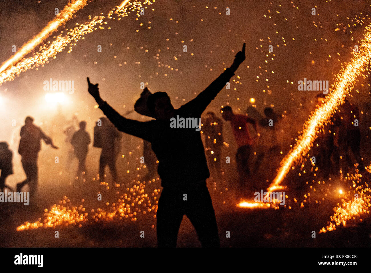 San Miguel de Allende, Mexico. 29th Sept 2018. A Mexican man celebrates as dozens of sky rockets explode around him in the chaos of the Alborada festival September 29, 2018 in San Miguel de Allende, Mexico. The unusual festival celebrates the cities patron saint with a two hour-long firework battle at 4am representing the struggle between Saint Michael and Lucifer. Credit: Planetpix/Alamy Live News - Stock Image
