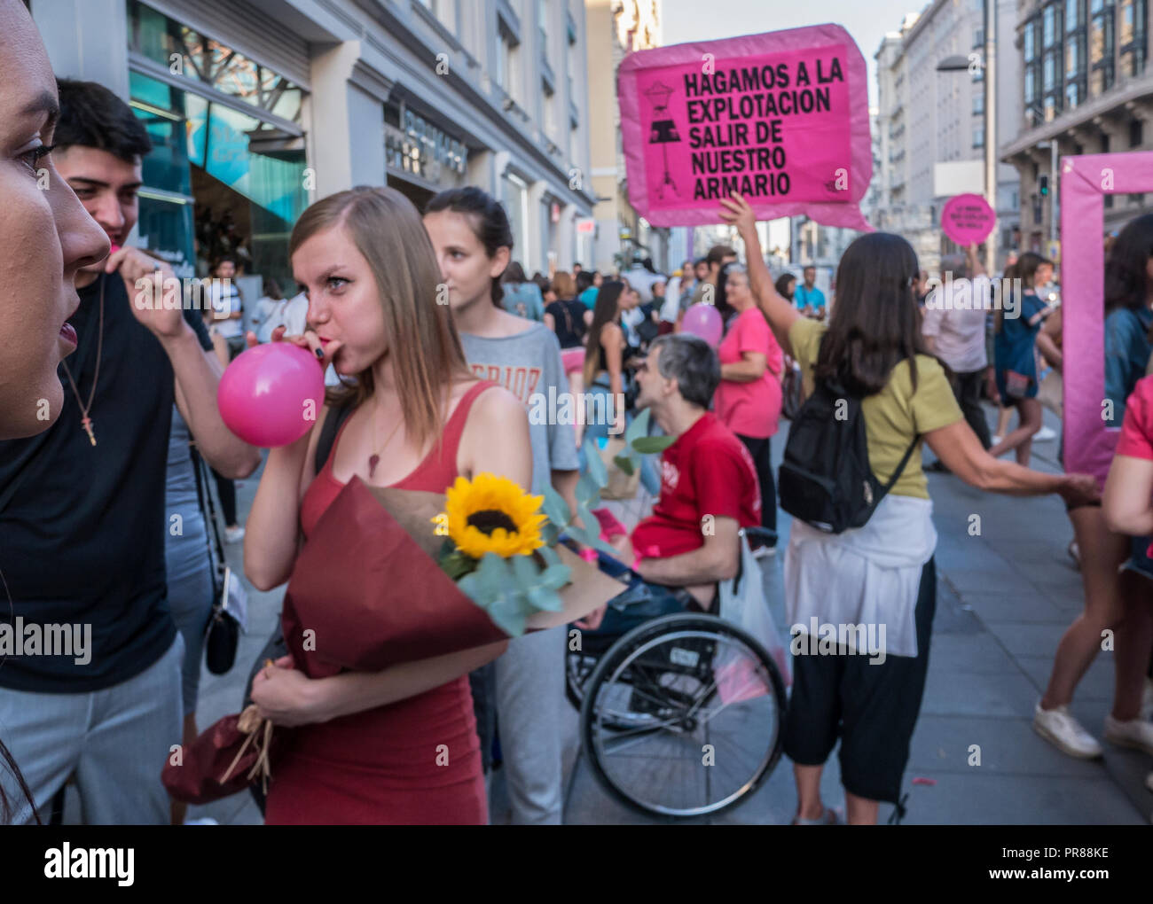 Madrid, Spain. 30 September 2018. A protest action against slavery in fashion industry took place in Gran Vía, the main street of Madrid, consisting of creating awareness around the explotation of people in fashion factories. The organizators gave passers by pink baloons to explode in front of the main comercial shops of the street. Credit: Lora Grigorova/Alamy Live News - Stock Image