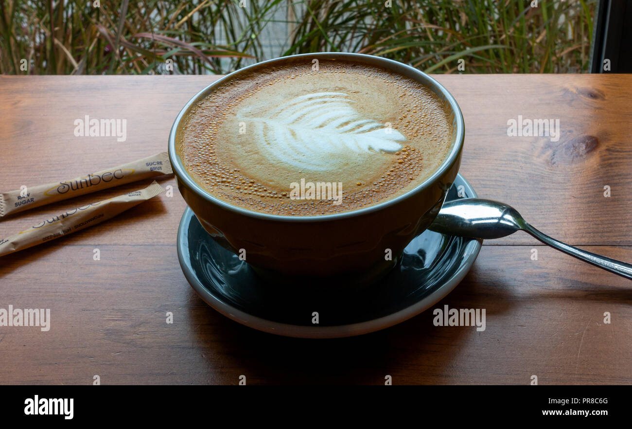 A large cappuccino in a bowl with sugar packets and a spoon Stock Photo