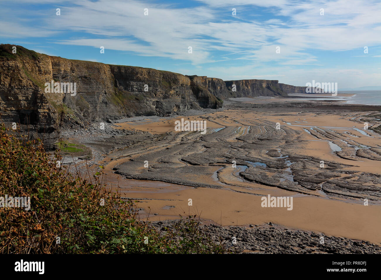 View south along the cliffs towards Monk nash point with the tide fully out exposing the eroded roack layers amid the sands on this 'Heritage' coast. - Stock Image