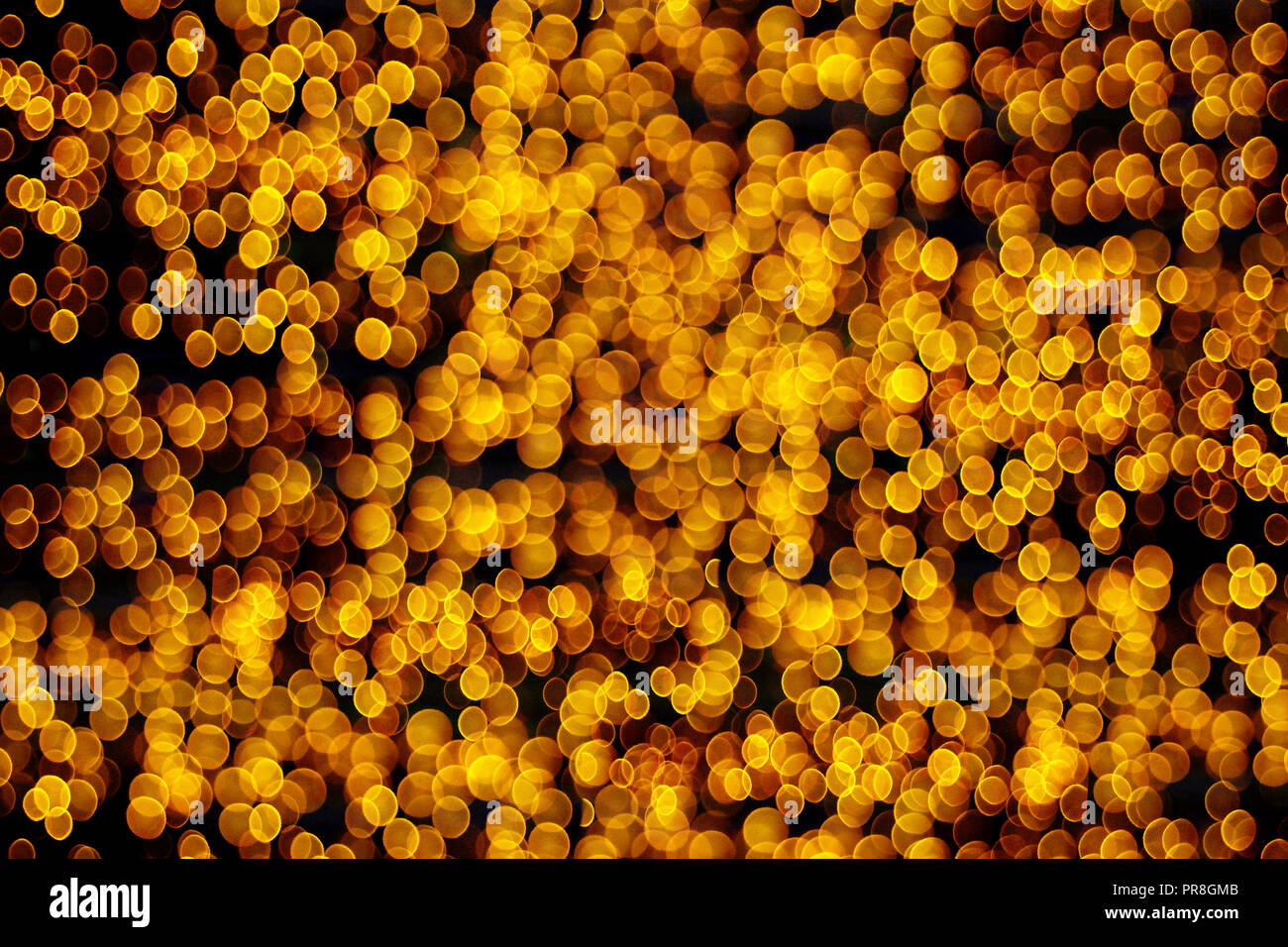Abstract Christmas lights background, golden glitter defocused texture - Stock Image