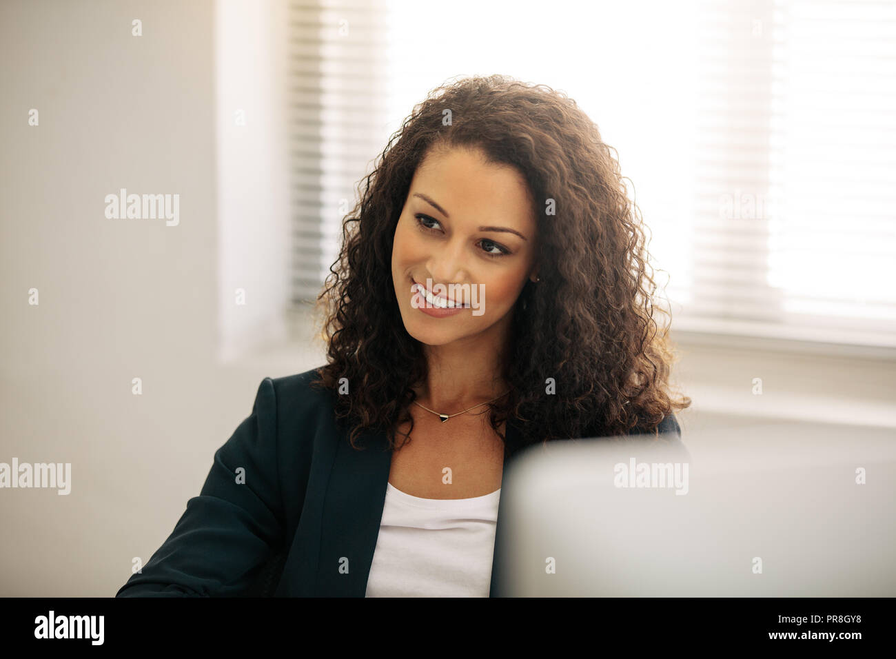 Close up of a smiling businesswoman in office. Curly haired businesswoman in formal clothes sitting at her desk in office. - Stock Image
