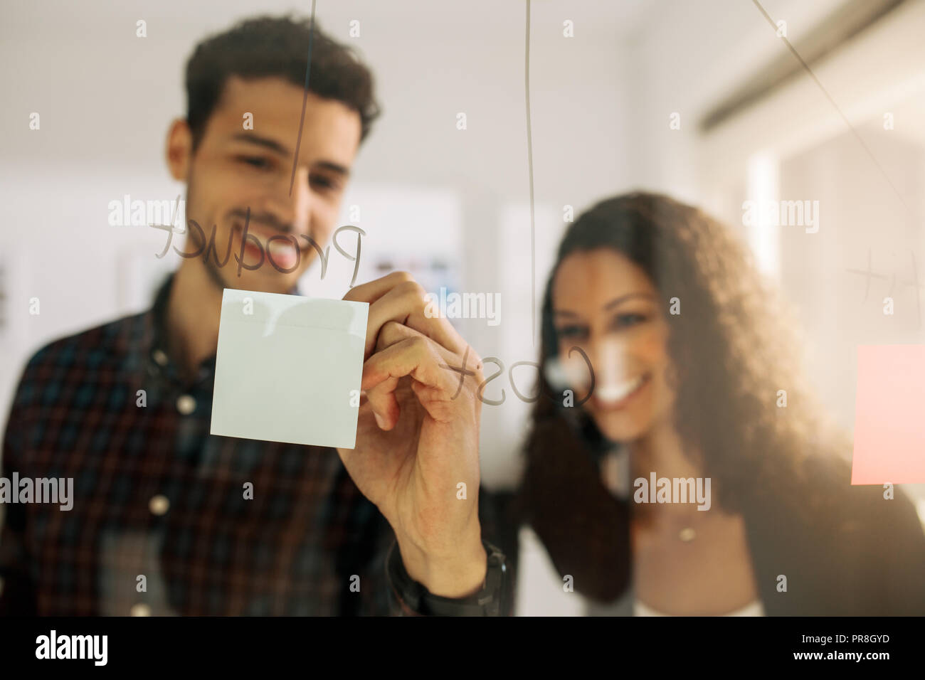 Business couple writing on sticky notes pasted on transparent glass wall in office. Office colleagues discussing business ideas and plans on a transpa - Stock Image