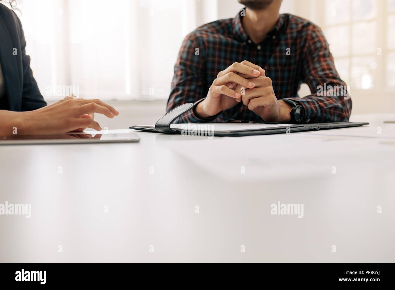 Close up shot focusing on hand gestures of business colleagues during a meeting. Two business people sitting at the table discussing work. - Stock Image