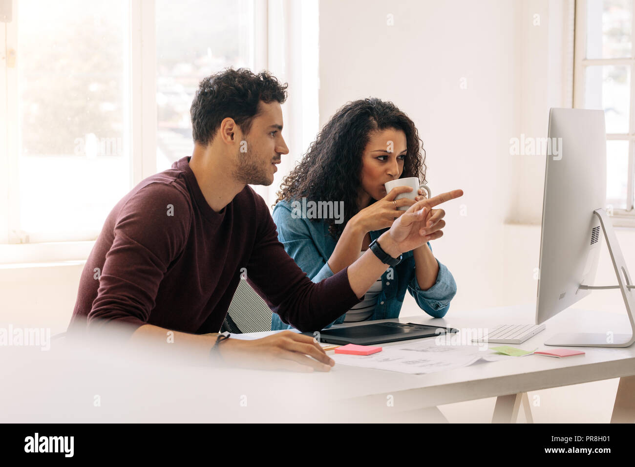 Businessman pointing towards the computer while discussing work with a business partner. Woman entrepreneur drinking coffee while discussing work with Stock Photo