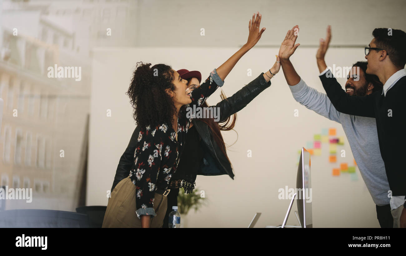 Business colleagues giving high five to each other standing in office. Team members celebrating success at work by giving high five. - Stock Image