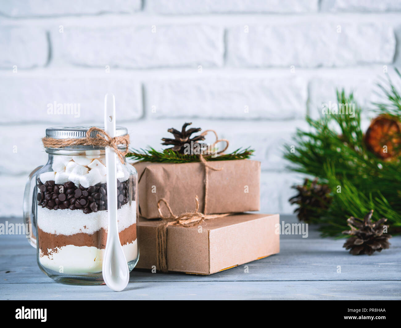 Hot chocolate mix in mason jar and rustic gift boxes on gray table ...