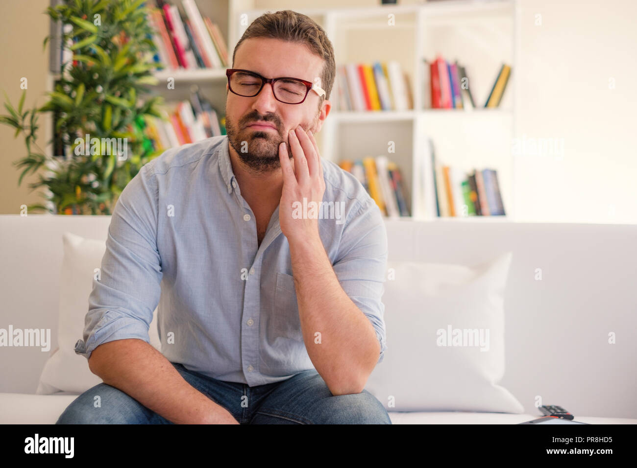 Man portrait feeling tooth ache at home - Stock Image