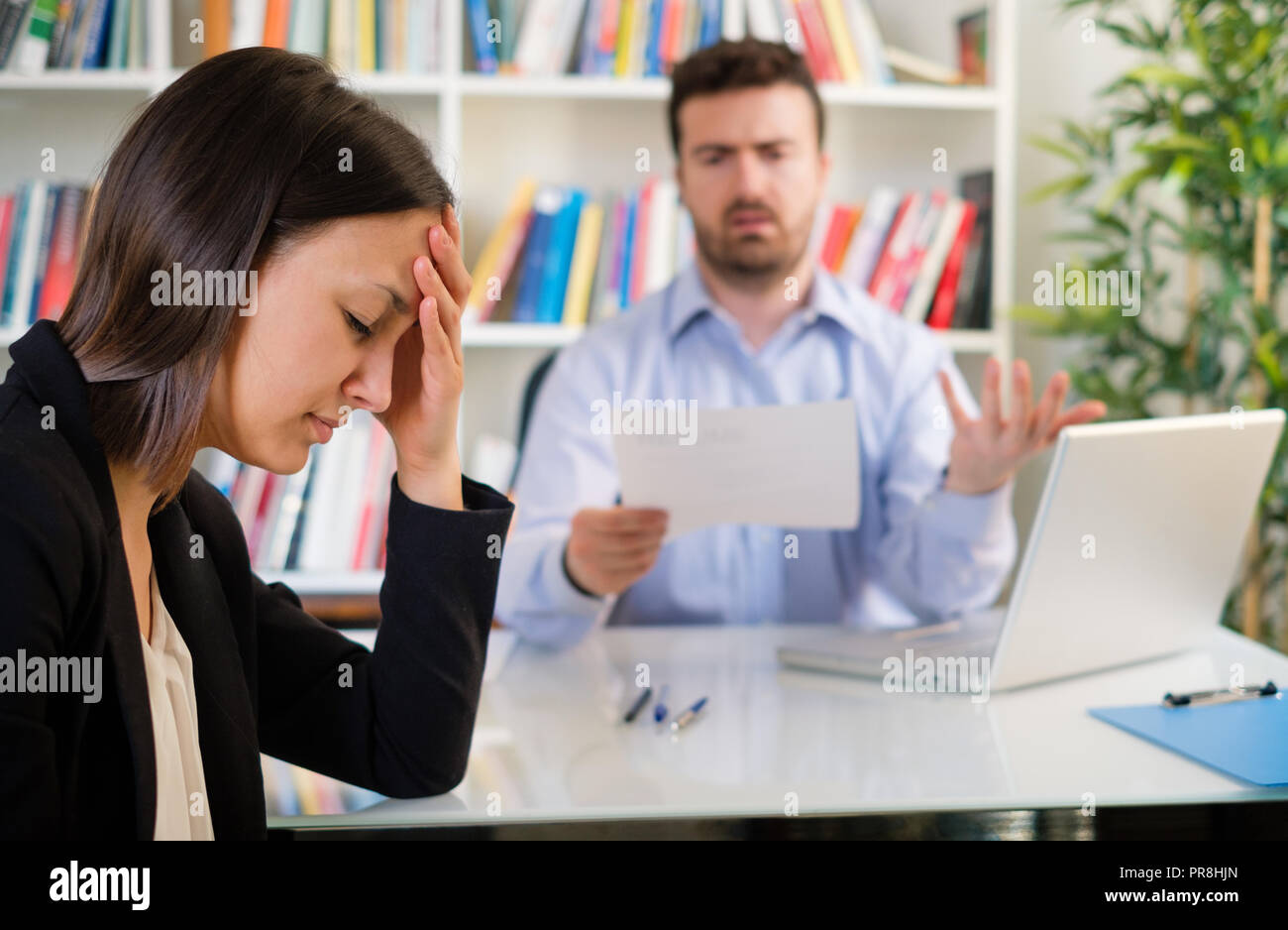 Angry boss blaming with rudeness young secretary - Stock Image