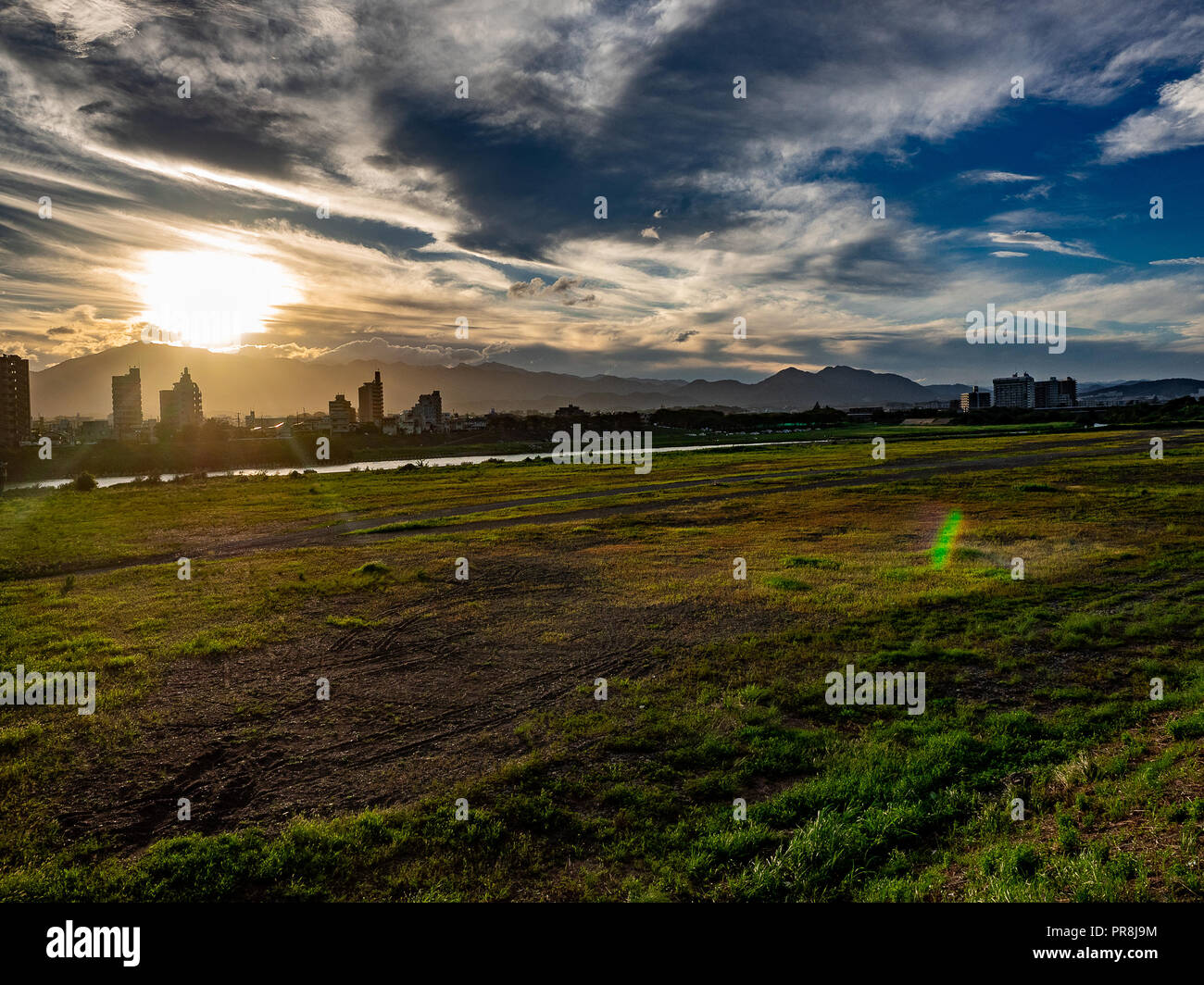 Looking out over the shore of the Sagami River near Ebina, Kanagawa Prefecture, Japan near sunset. - Stock Image