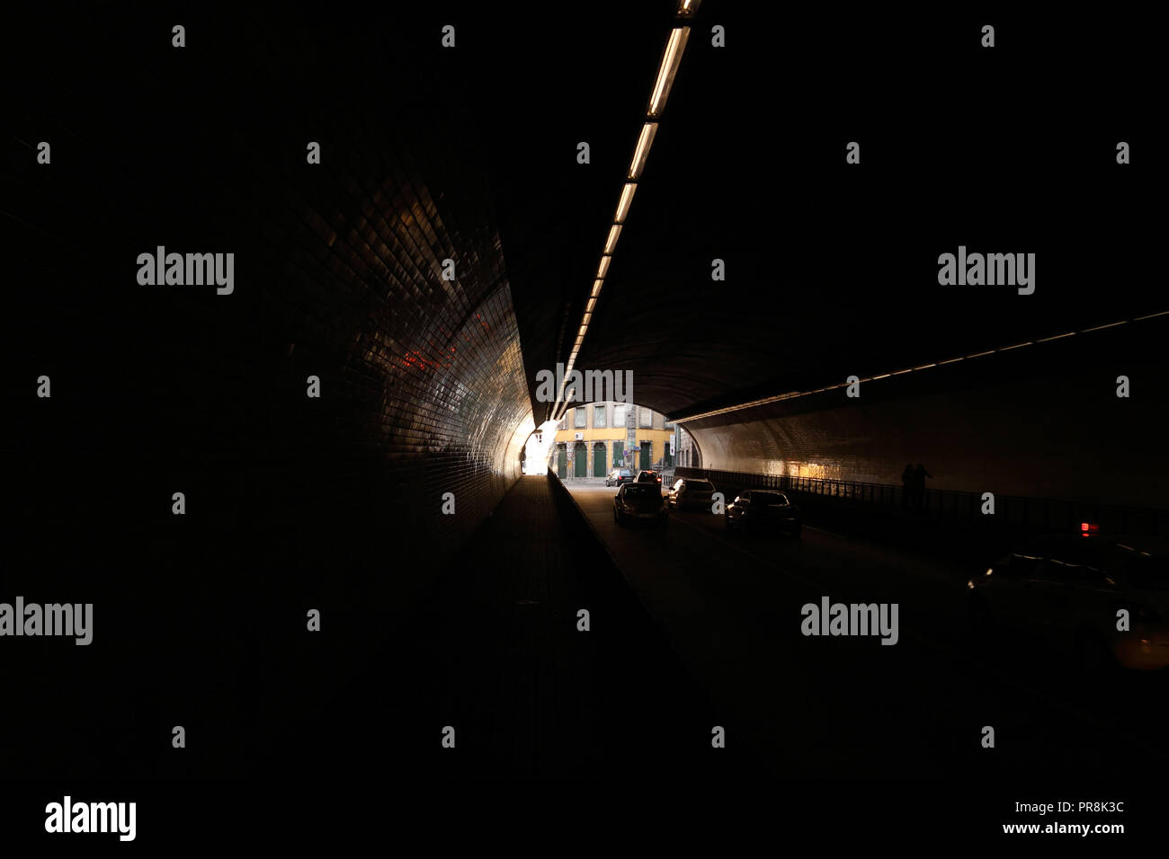 Perspective view through the dark tunnel of Ribeira (Porto, Portugal) seeing traffic and interesting light - Stock Image