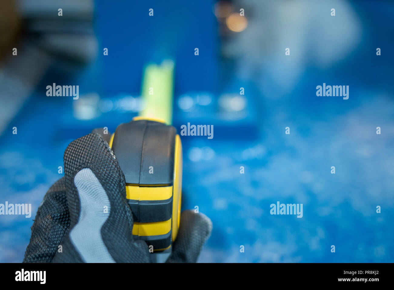 Measure the distance by hand with a tape measure in the industry - Stock Image