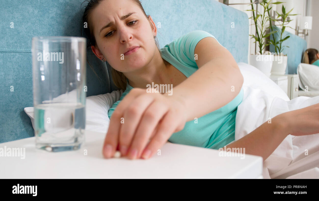 Portrait Of Young Sick Woman Lying In Bed And Taking Pill From Bedside Table