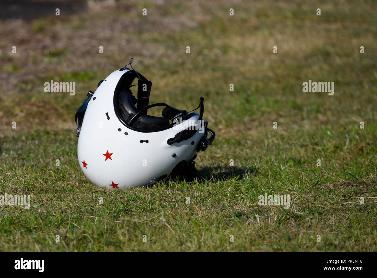 Pilot's helmet sitting, laying on the ground before or after a flight. Flying helmet in isolation. Isolated. Russian red stairs. Flight helmet alone - Stock Image
