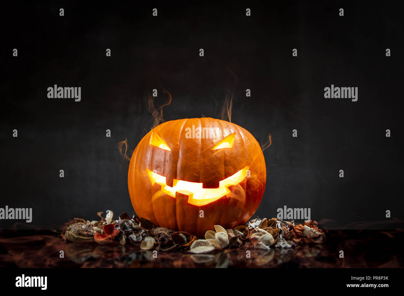 Composition of pumpkin on black background with glowing smoke. Horizontal orientation - Stock Image